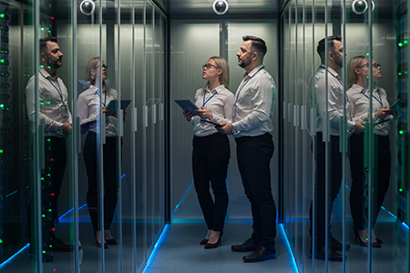 Man and women in data center looking a rack of servers